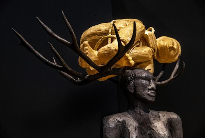Sculpture of a woman carrying a child in antlers sprouting from her head