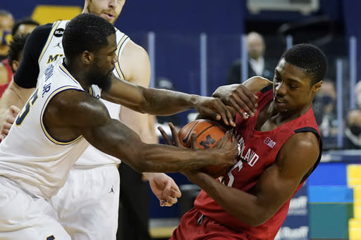 Michigan guard Chaundee Brown (15) and Maryland forward Jairus Hamilton (25) try controlling the ball during the first half of an NCAA college basketball game, Tuesday, Jan. 19, 2021, in Ann Arbor, Mich. (AP Photo/Carlos Osorio)