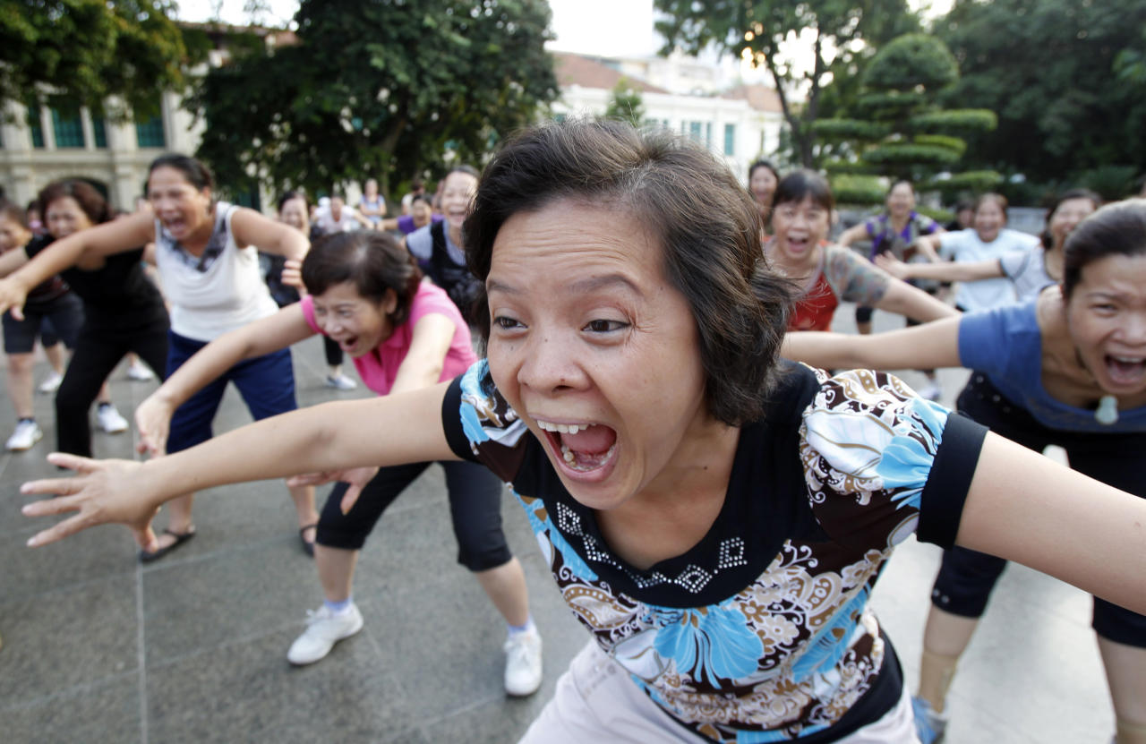 Members of the Laughter Yoga club practise laughing during morning exercise at a public park in Hanoi September 24, 2011. For the past two years, several hundred people have been gathering each morning at a public park in central Hanoi to practise laughing under the instruction of yoga master Le Anh Son in the belief that this will help them to be happier, fight disease and relief the stresses of daily life. Laughter yoga was launched in 1995 by Dr. Madan Kataria, a physician, in India and there are now more than 6,000 clubs in 60 countries, Son said. REUTERS/Kham