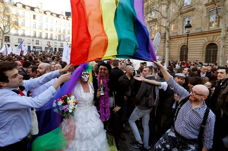 "People gather to celebrate the passage of a law allowing same-sex couples to marry and adopt children, in Paris April 23, 2013. French lawmakers passed a bill on Tuesday, a flagship reform pledge by French President which sparked often violent street protests and a rise in homophobic attacks. The law legalises gay marriage and gives gay and lesbian couples adoption rights. Sign reads, ""Yes to Equality"". REUTERS/Charles Platiau (FRANCE - Tags: POLITICS SOCIETY)"