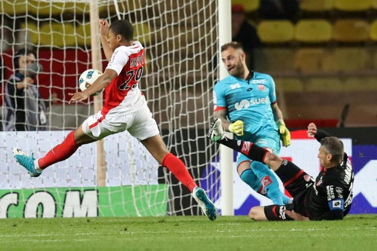 Monaco's Kylian Mbappe (L) shoots during their match against Dijon on April 15, 2017 at the Louis II Stadium in Monaco