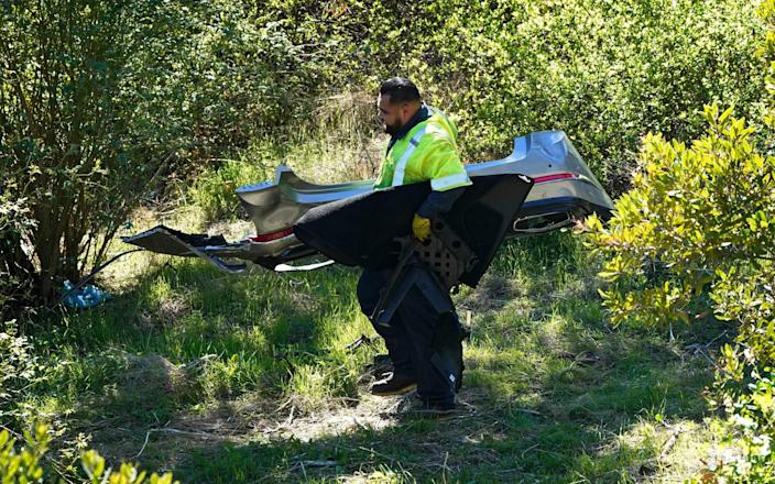 A worker moves debris after a rollover accident involving golfer Tiger Woods - AP