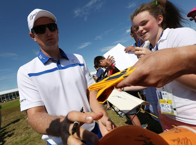 Justin Rose of England signs autographs for fans during a practice round ahead of the British Open Golf championship at the Royal Liverpool golf club, Hoylake, England, Tuesday July 15, 2014. The British Open Golf championship starts Thursday July 17. (AP Photo/Jon Super)