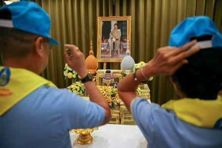People wear blue caps and yellow foulards next to a portrait of Thailand's King Maha Vajiralongkorn during a ceremony to become king's volunteers at the Bureau of the Royal Household in Bangkok, Thailand, August 10, 2018. REUTERS/Athit Perawongmetha/File Photo