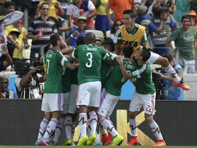 Mexico's players celebrate after scoring their first goal during the World Cup round of 16 soccer match between the Netherlands and Mexico at the Arena Castelao in Fortaleza, Brazil, Sunday, June 29, 2014. (AP Photo/Marcio Jose Sanchez)