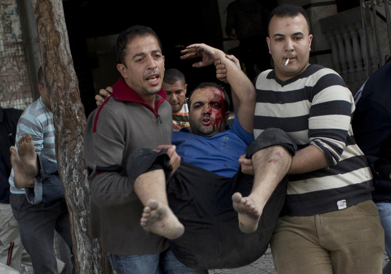 Palestinians carry injured people out of a media center in Gaza City that was hit by an Israeli strike for the second time in two days Monday, Nov. 19, 2012. Palestinian militant group Islamic Jihad says the strike on the building killed one of its top militant leaders. (AP Photo/Bernat Armangue)