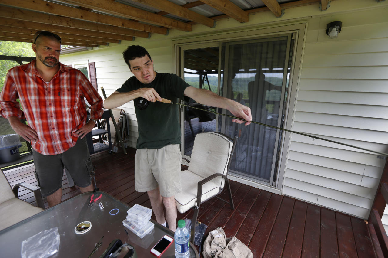 In this June 25, 2013 photo, Richard Norris, right, shows friend Andrew Kahle, left, how to load line into a fly fishing rod at Norris' home in Hillsville, Va. Norris, whose face was disfigured by a gunshot, spent 15 years as a recluse, but now the 37-year-old is doing things he never would have before. (AP Photo/Chuck Burton)