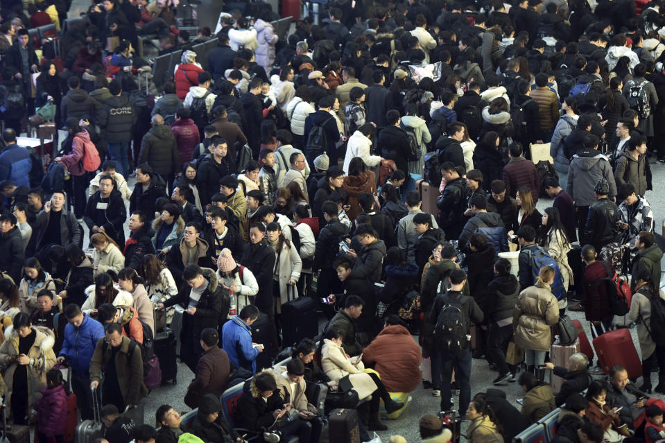 In this Jan. 28, 2019, photo, Chinese travelers wait for their trains at a railway station in Hangzhou in east China's Zhejiang province. The world's largest annual migration has began in China with millions of Chinese are traveling to their hometowns to celebrate the Lunar New Year on Feb. 5 this year which marks the Year of the Pig on the Chinese zodiac. (Chinatopix via AP)