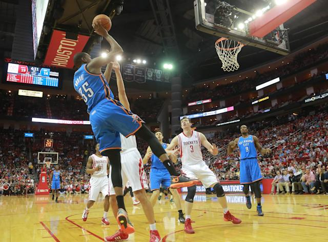 Oklahoma City Thunder forward Kevin Durant, left, puts up a shot against the Houston Rockets during an NBA basketball game in Houston Friday, April 4, 2014. (AP Photo/Richard Carson)