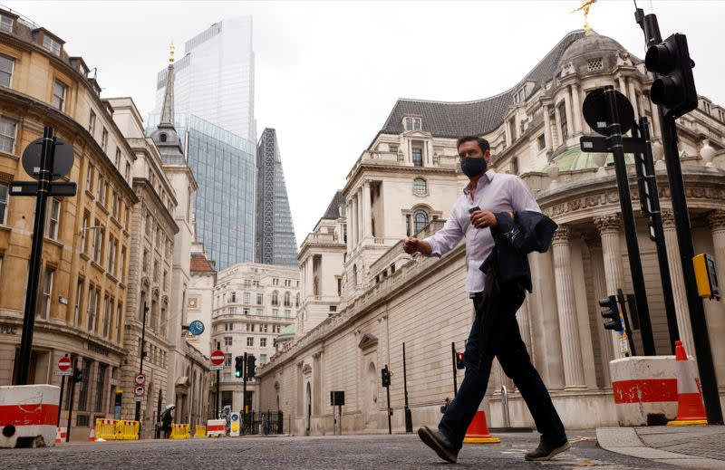 A man wearing a face mask crosses the road in the City of London financial district amid the outbreak of the coronavirus disease (COVID-19)