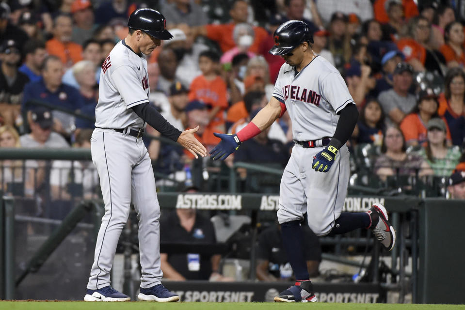 Cleveland Indians' Cesar Hernandez, right, clasps hands with third base coach Mike Sarbaugh after hitting a solo home run during the seventh inning of the team's baseball game against the Houston Astros, Wednesday, July 21, 2021, in Houston. (AP Photo/Eric Christian Smith)