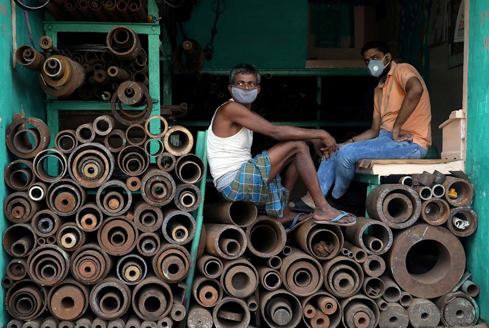 Workers wearing protective face masks sit inside a shop in Kolkata (REUTERS/Rupak De Chowdhuri)