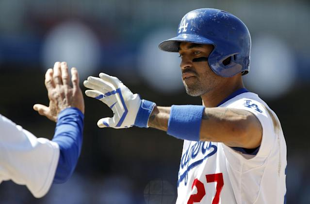 Los Angeles Dodgers' Matt Kemp gets a high-five from first base coach Davey Lopes after hitting an RBI-single to score Yasiel Puig in the sixth inning of a baseball game against the San Francisco Giants, Saturday, May 10, 2014, in Los Angeles. (AP Photo/Alex Gallardo)