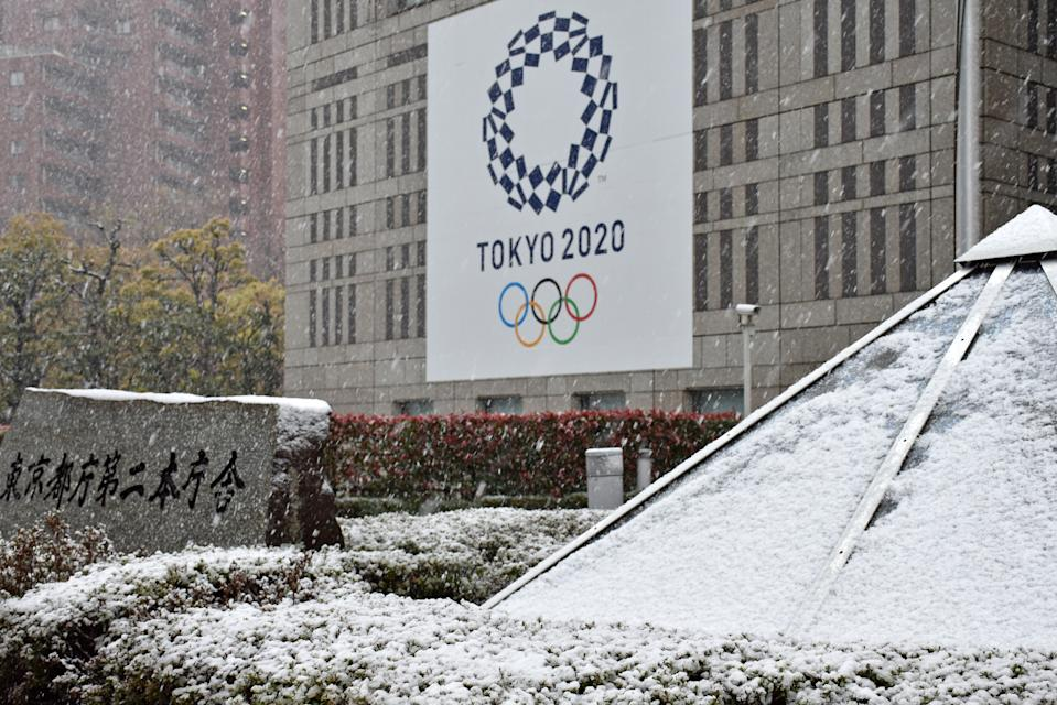TOKYO, JAPAN - MARCH 29, 2020: A banner promoting the Tokyo 2020 Olympic games is on display outside a building in Shibuya during a spring snowfall. Snow in late March is a rare sight in Tokyo. The Tokyo 2020 Olympic games have been postponed in connection with the global pandemic of the novel coronavirus (COVID-19). Alexei Zavrachayev/TASS (Photo by Alexei Zavrachayev\TASS via Getty Images)