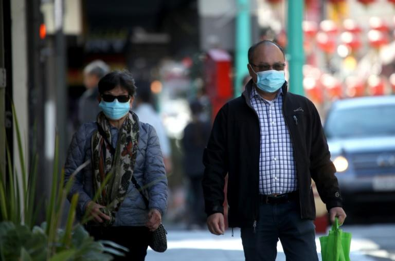 People wear surgical masks as they walk in San Francisco's Chinatown in February 2020 amid the coronavirus outbreak