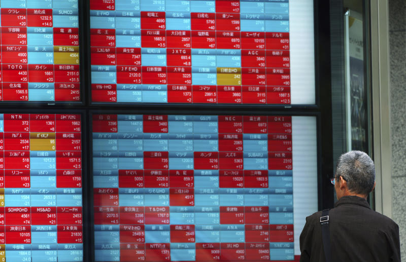 A man looks at an electronic stock board showing Japan's Nikkei 225 index at a securities firm in Tokyo Friday, Nov. 16, 2018. Shares were mixed in early trading in Asia on Friday on revived concerns over the prospects for a breakthrough in trade tensions between the U.S. and China. (AP Photo/Eugene Hoshiko)
