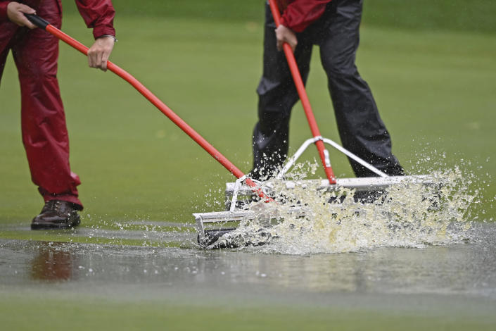 Workers push water off the putting green on the second hole during the final round of the Marathon LPGA Classic golf tournament at Highland Meadows Golf Club in Sylvania, Ohio, Sunday, July 11, 2021, in Sylvania, Ohio. (AP Photo/David Dermer)