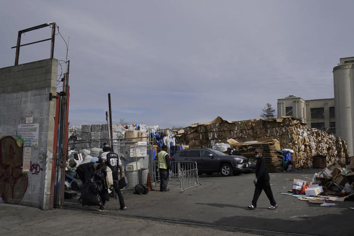 People walk inside a recycling location in Oakland, Calif., Thursday, Feb. 18, 2021. Disadvantaged communities in America are disproportionately affected by pollution from industry or waste disposal, but their complaints have few outlets and often reach a dead end. (AP Photo/Jeff Chiu)