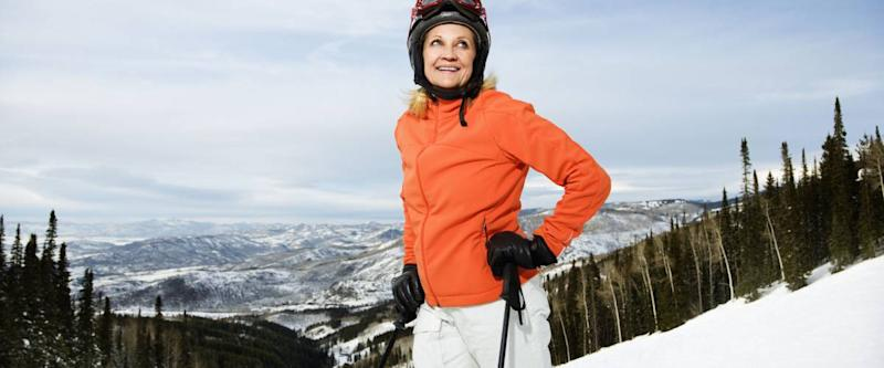 Smiling skier on ski slope in Colorado leaning on her poles with mountains in background. Horizontal shot.