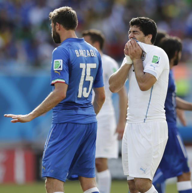 Uruguay's Luis Suarez, right, holds his teeth after running into Italy's Giorgio Chiellini's shoulder during the group D World Cup soccer match between Italy and Uruguay at the Arena das Dunas in Natal, Brazil, Tuesday, June 24, 2014. (AP Photo/Petr David Josek)