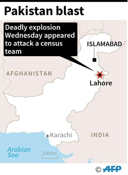 Pakistani security officials collect evidence from the scene of an attack on a census team in Lahore