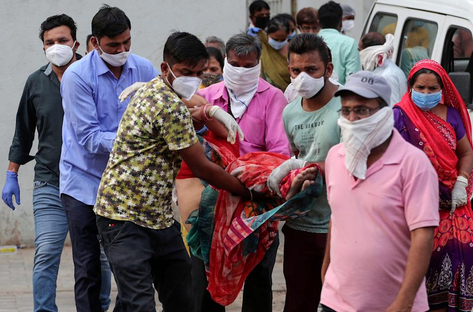 <p>Relatives carry a woman who fainted after seeing the body of her husband at a hospital in Ahmedabad, India</p> (AP)