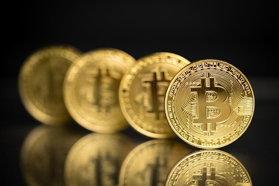 Philippines, August 25 - 2018: Row of gold plated Bitcoin physical form imitation as a decentralized digital currency which enables instand payment to anyone around the world. Original bitcoin software was invented by Satoshi Nakamoto and being used as open source licensing. This close up shot of bitcoin to symbolize bitcoin market, modern tech, crypto currency, finance, stock and trading over internet.