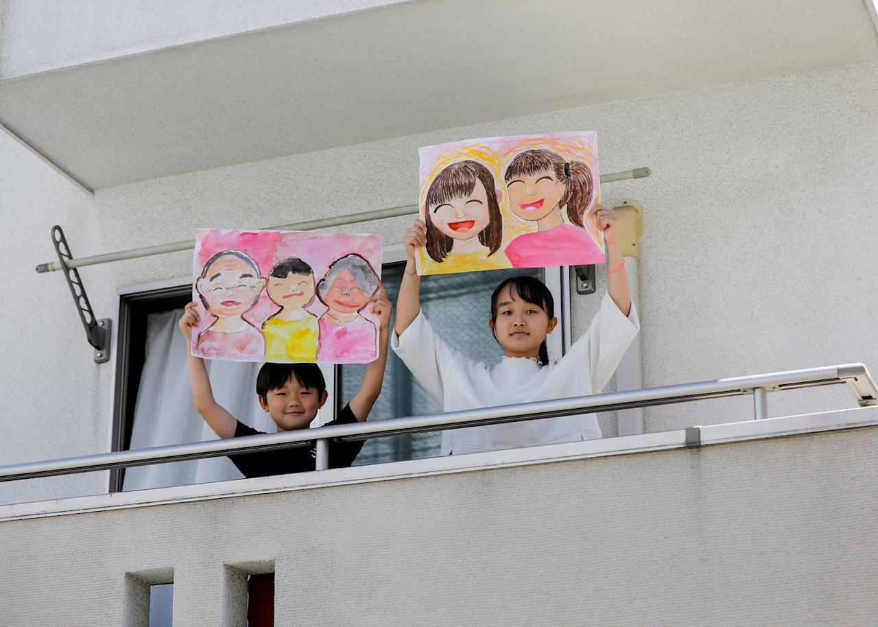 "Reku Matsui, 8, and Yaya Matsui, 12, pose for a photograph while holding pictures that they drew during the coronavirus disease (COVID-19) outbreak, as they stand on the balcony of their home in Tokyo, Japan, April 19, 2020. ""I miss being with my grandmother and my grandfather. Also, I want to go to my grandmother's house,"" said Reku, who drew a picture of himself standing in between his two smiling grandparents. Yaya, who drew a picture of herself and a friend said ""what I want to do the most right now is hang out with my friends."" REUTERS/Kim Kyung-Hoon     SEARCH ""CORONAVIRUS DRAWING"" FOR THIS STORY. SEARCH ""WIDER IMAGE"" FOR ALL STORIES. TPX IMAGES OF THE DAY"