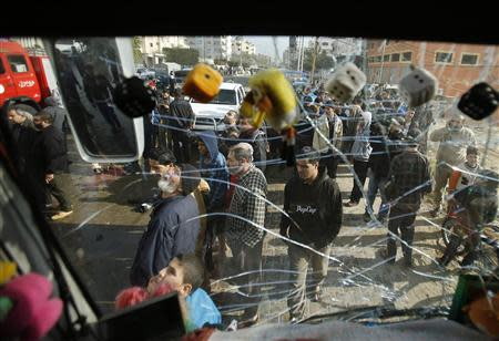 Palestinians are pictured through the damaged windscreen of a bus as they gather at the scene of an Israeli air strike, which hit a motorcycle, in the northern Gaza Strip January 19, 2014. REUTERS/Mohammed Salem