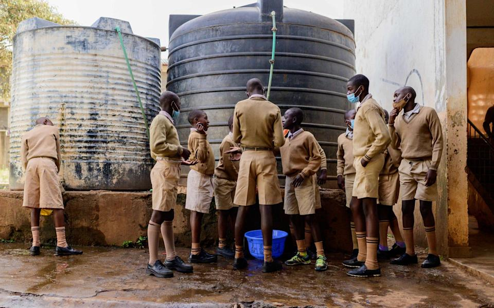 Students fill a container with water to clean the classroom, as public schools final reopen in Kenya following a nine month closure - GORDWIN ODHIAMBO/AFP