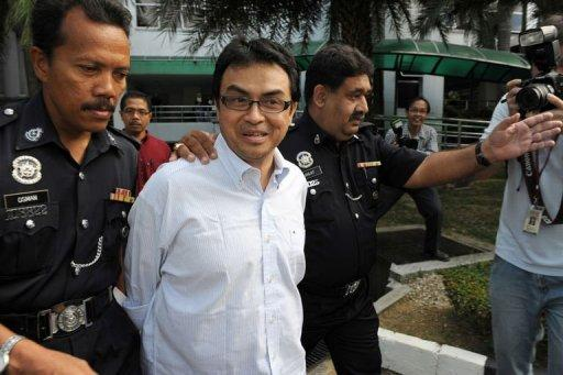 Abdul Razak Baginda (C), a high-profile political analyst, walks towards the court room in police custody in Shah Alam