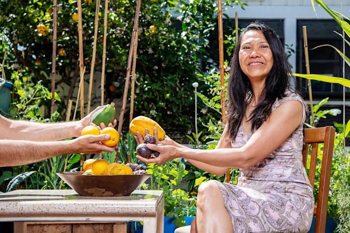 Thuy Tran exchanges fruit with someone