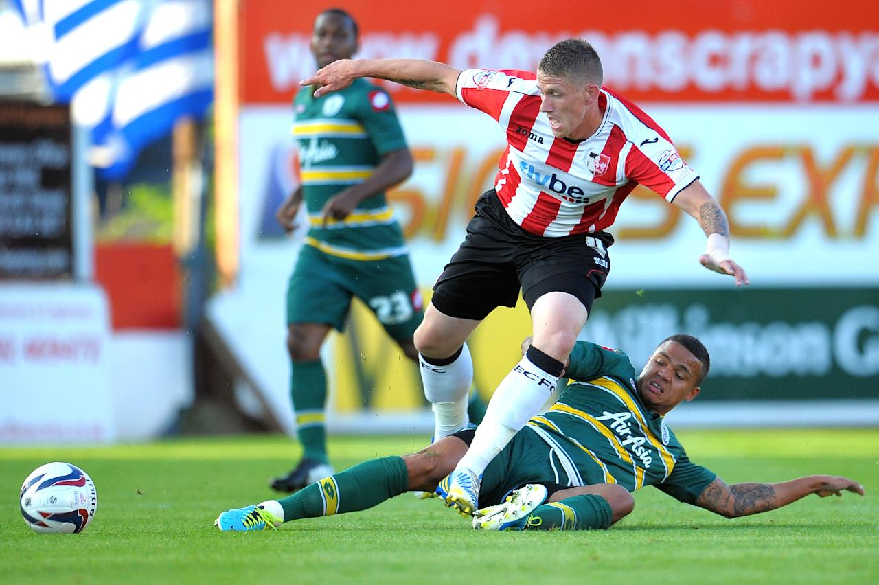 Exeter's Scot Bennett is tackled by Queens Park Rangers' Jermaine Jenas during the Capital One Cup, First Round match at St James' Park, Exeter.