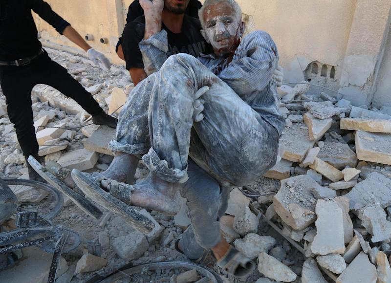 Rescue retrieve a man from under rubble in Aleppo's Sakhour district on July 25, 2014, after a Syrian government helicopter allegedly dropped a barrel bomb
