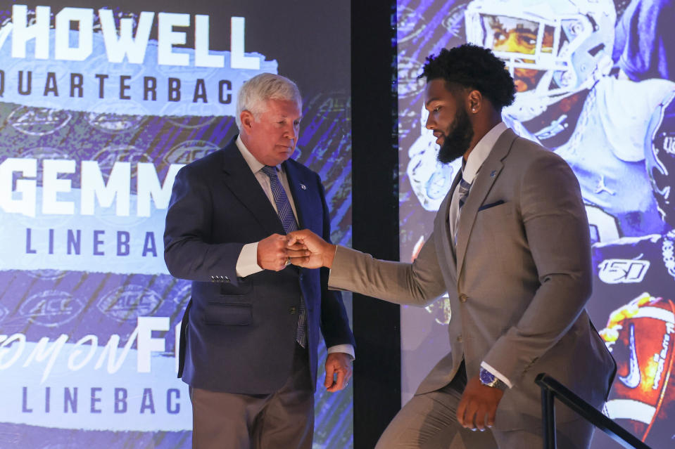 North Carolina head coach Mack Brown, left, fist bumps linebacker Tomon Fox during the NCAA college football Atlantic Coast Conference media days in Charlotte, N.C., Wednesday, July 21, 2021. (AP Photo/Nell Redmond)