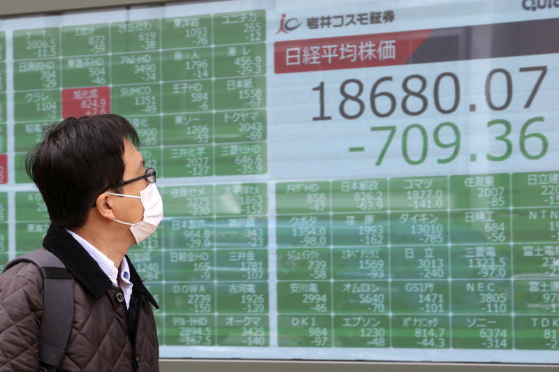 A man looks at an electronic stock board of a securities firm in Tokyo, Monday, March 30, 2020. Asian shares started the week with further losses as countries reported surging numbers of infections from the coronavirus that has prompted shutdowns of travel and business in many parts of the world.(AP Photo/Koji Sasahara)