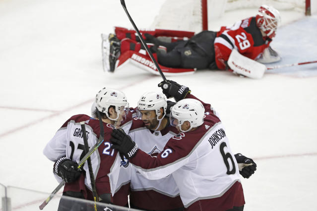 Colorado Avalanche defensemen Ryan Graves (27) and Erik Johnson (6) celebrate with center Pierre-Edouard Bellemare (41) after Bellemare scored against New Jersey Devils goaltender Mackenzie Blackwood, (29) during the third period of an NHL hockey game, Saturday, Jan. 4, 2020, in Newark, N.J. The Avalanche won 5-2. (AP Photo/Kathy Willens)