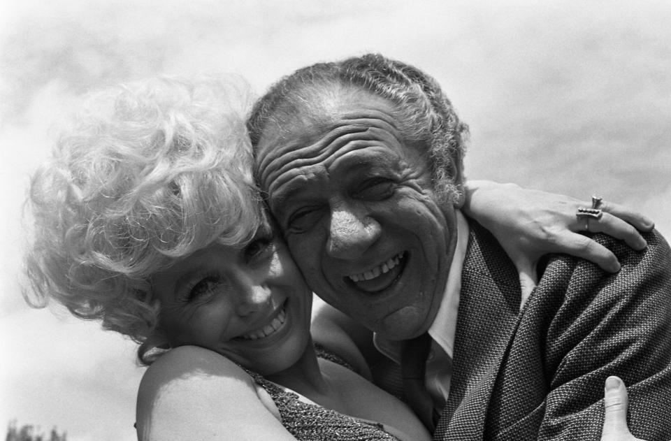 """British comedy actor Sid James gets a friendly farewell cuddle from his British co-star Barbara Windsor as they complete the last day of shooting of the film """"Carry On Girls"""", at Pinewood Studios, England, May 25, 1973. (AP Photo/Robert Dear)"""