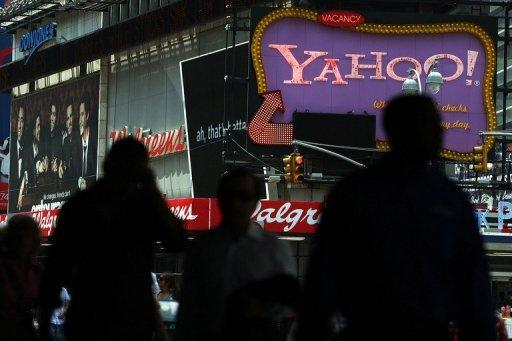 Pedestrians walk by a Yahoo! sign in Times Square