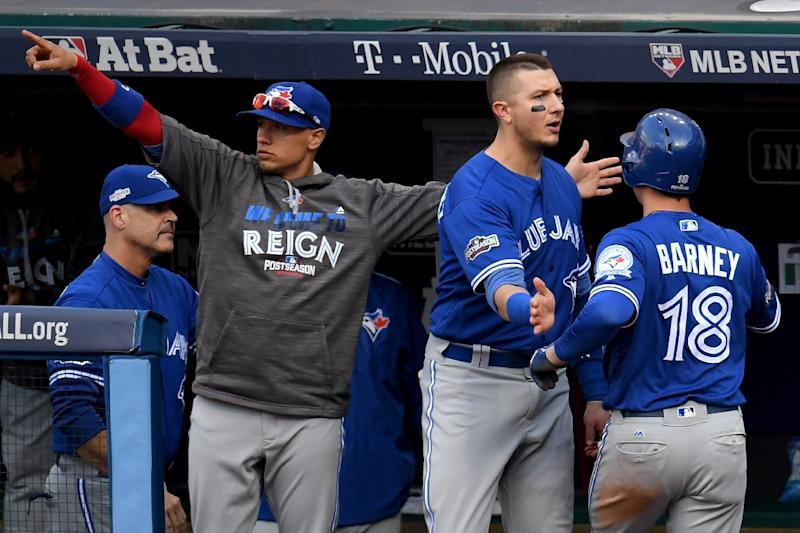 Darwin Barney (R) of the Toronto Blue Jays celebrates with teammates after scoring a run off of a double hit by Josh Donaldson in the third inning against Josh Tomlin of the Cleveland Indians, in Cleveland, Ohio, on October 15, 2016 (AFP Photo/Jason Miller)
