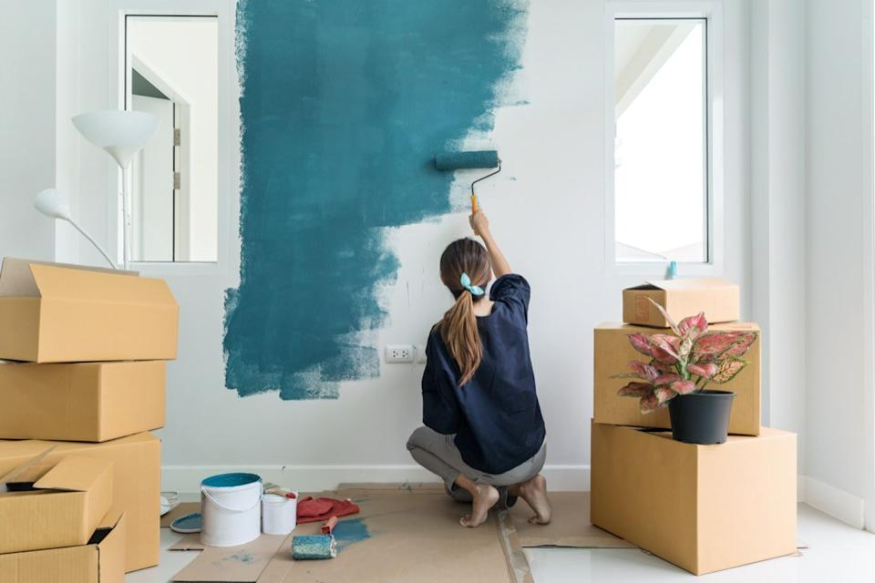 young white woman in empty home painting wall green