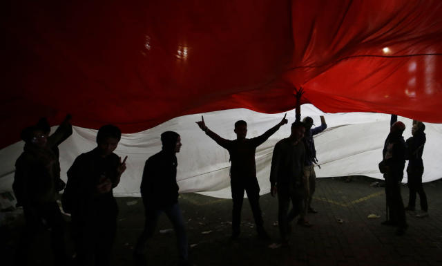 Supporters of the losing presidential candidate walk under a giant Indonesia national flag in Jakarta, Indonesia. Wednesday, May 22, 2019. Indonesian President Joko Widodo said authorities have the volatile situation in the country's capital under control after a number of people died Wednesday in riots by supporters of his losing rival in last month's presidential election. (AP Photo/Achmad Ibrahim)