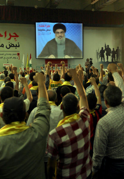 "Hezbollah supporters, raise their hands in salute as Hezbollah leader Sheik Hassan Nasrallah speaks on a screen via a video link from a secret place, during a rally to mark the ""wounded resistant's day,"" in the southern suburb of Beirut, Lebanon, Friday, June 14, 2013. Nasal said his group will continue to fight in Syria ""wherever needed,"" and said he has made a ""calculated"" decision to defend Syria and is ready to bear all consequences. (AP Photo/Bilal Hussein)"