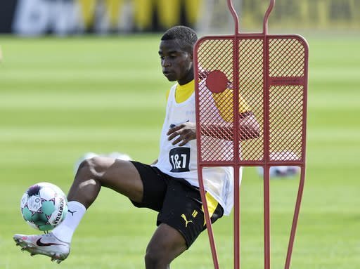 FILE - In this Monday, Aug. 3, 2020 file photo, Dortmund's Youssoufa Moukoko controls the ball during the first training session of German Bundesliga club Borussia Dortmund at the training grounds in Dortmund, Germany. Moukoko will be eligible to make his Bundesliga debut against Hertha Berlin on Saturday, Nov. 21, 2020, one day after his 16th birthday. (AP Photo/Martin Meissner)