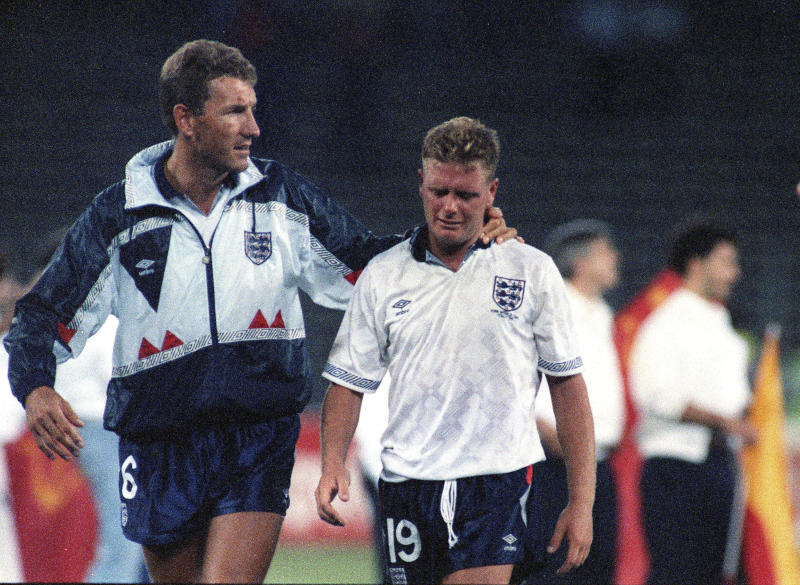 FILE - The July 4, 1990 file photo shows England's Paul Gascoigne crying as he is escorted off the field by team captain Terry Butcher, after his England lost a penalty shoot-out in the semi-final match of the World Cup against West Germany in Turin, Italy. At the fourth time of asking, England finally won a penalty shootout at the World Cup against Colombia on Tuesday, July 3. (AP Photo/Roberto Pfeil, File)