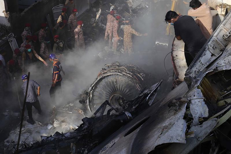 Rescue workers search for bodies and survivors amid the wreckage of the Pakistan International Airlines plane: EPA