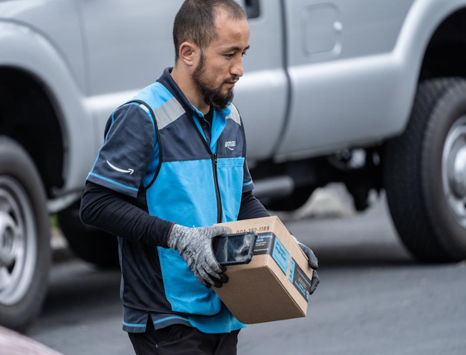 Berks County, Pennsylvania, USA, April 26, 2020-Amazon.com delivery person wearing gloves packages on suburban street
