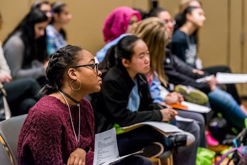 Young women sit in an audience listening to a speaker.