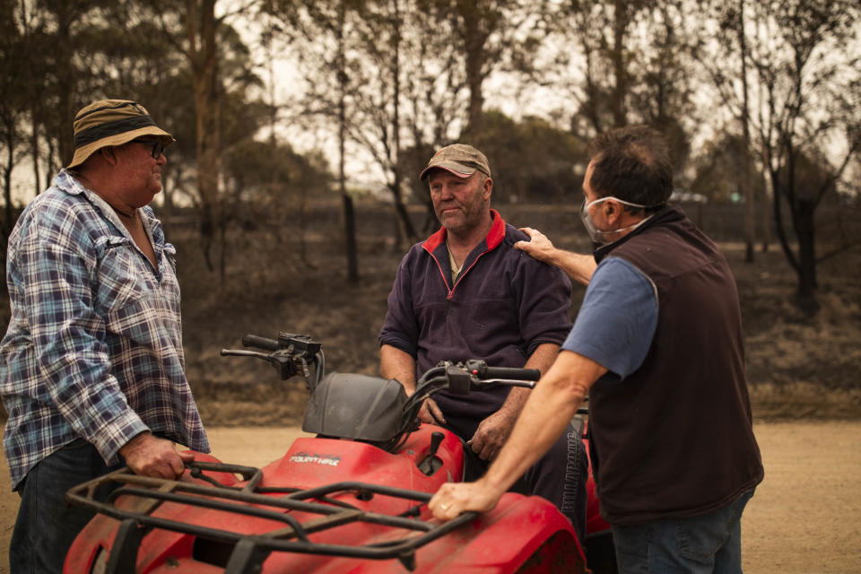 Steve Shipton (centre) is consoled by fellow farmers Bernie Smith (left) and Peter Mercieca in Coolagolite, NSW, Wednesday, January 1, 2020. Source: AAP