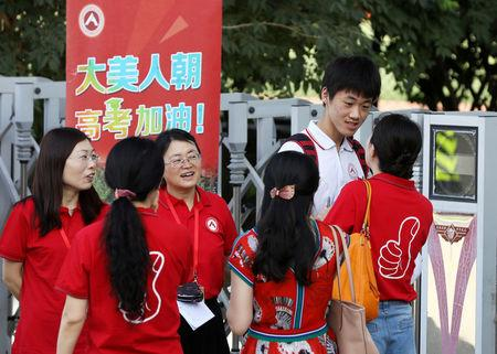 """Teachers in red tee-shirts talk with a student before he enters the venue for the annual national college entrance examination, or """"gaokao"""", in Beijing, China June 7, 2018.  China Daily via REUTERS"""
